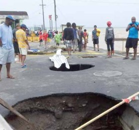 Sunken holes in the road next to the capital main market caused by Storm Erika.