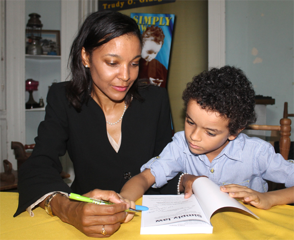 "Trudy Glasgow and son, Ethan, signing copies at last week Thursday's launch of ""Simply Law"". [Photo: Stan Bishop]"