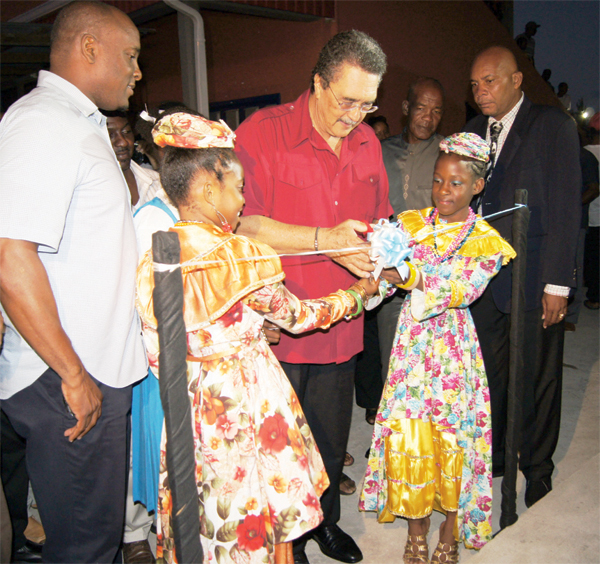 Prime Minister and Parliamentary representative for Vieux Fort South Dr. Kenny Anthony cutting the ribbon to officially put on the lights. [Photo: Anthony De Beaville]