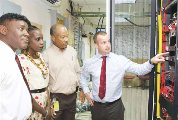 Image: Digicel Business Solutions Director (Eastern Caribbean), Martin Keogh, explains to Acting QEH CEO, Louise Bobb, and QEH IT Manager, Cameron Connolly, how the AVAYA-powered Unified Communication platform will benefit the medical and administrative staff while Digicel Barbados Strategic Business Development Director, Oliver Haynes, looks on.