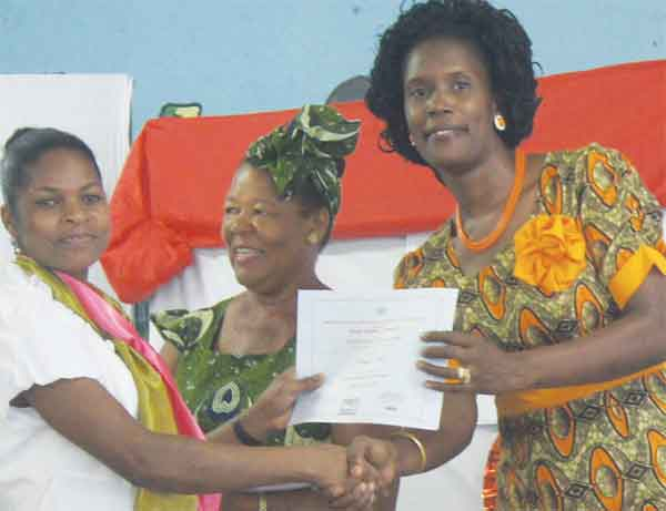 Garment construction/Information technology student receiving certificatefrom Ministry of Education staff.