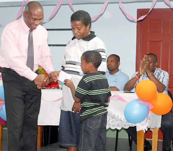 Education Minister Dr. Robert Lewis presents bursaries