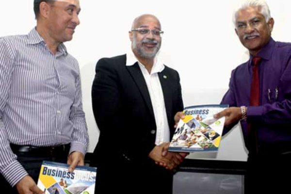 AMA's Lokesh Singh (far right) presents copies of the new OECS Business Focus Magazine to Dr. Didacus Jules and Gordon Charles. [Photo: Stan Bishop]