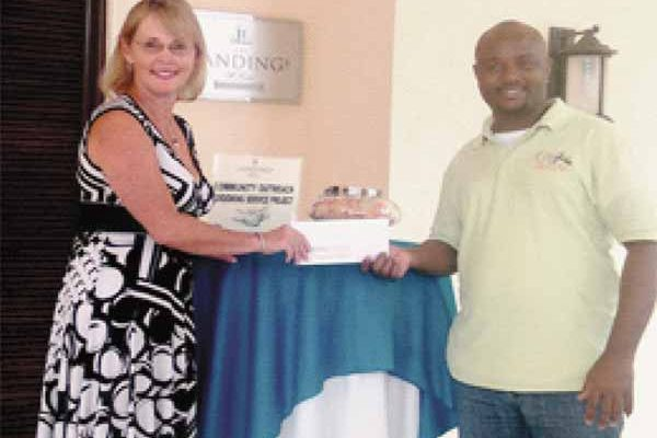 General Manager, Kathleen Taylor presenting donaion cheque to Cutty Ranks.