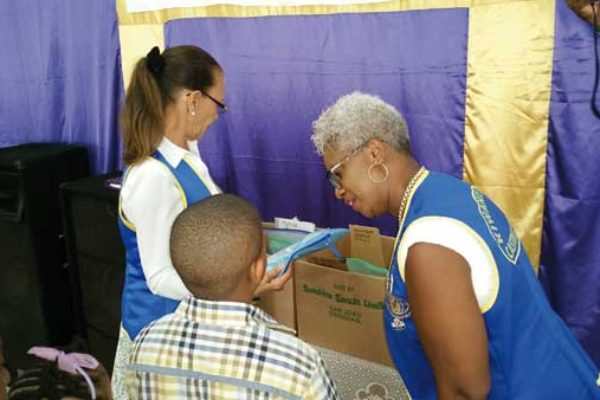 Kiwanis President Louise Vite' presenting supplies to a student from the Guesneau community.