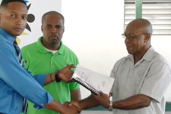Image of Dalson (right) receiving plans for the project