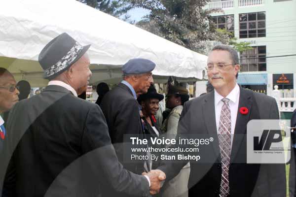 Image: Prime Minister Dr. Kenny Anthony greets World War II veterans at Derek Walcott Square.