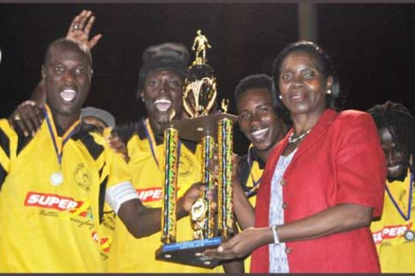 District representative for Gros Islet Emma Hippolyte presenting the championship trophy to Super J Northern United. (PHOTO: PHOTO: GIFL)