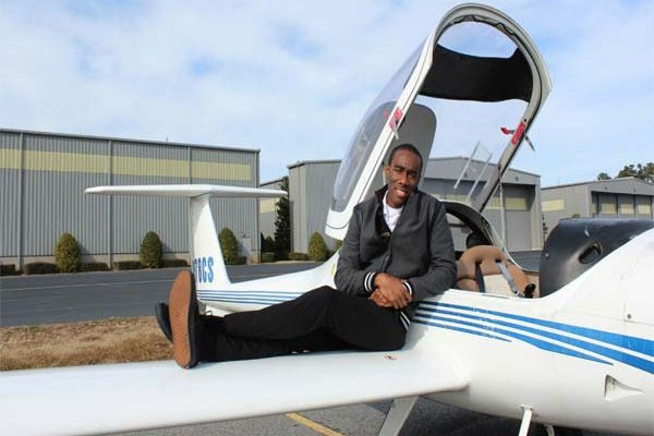 Tevin Belasco relaxes on the wing of an aircraft....his dream is to fly commercially.