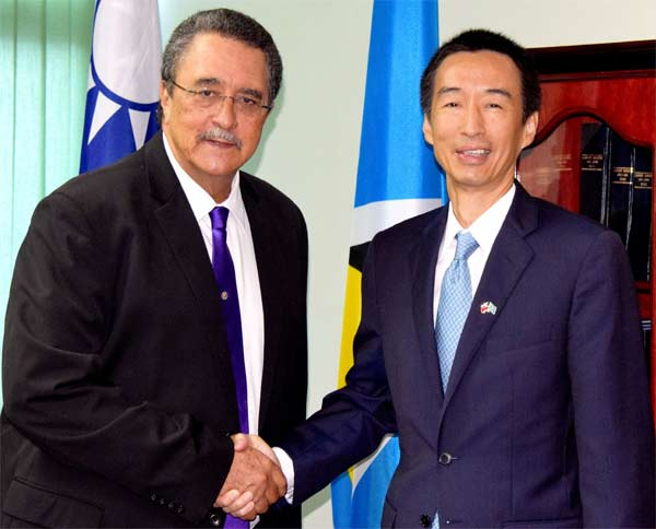 Image: Ambassador Mou and Prime Minister Anthony shake hands at the cheque presentation ceremony.