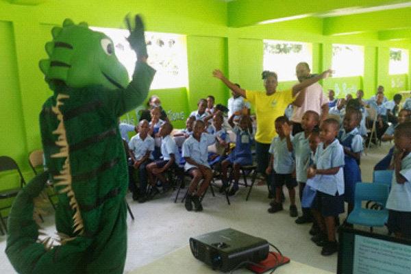 img: Igy the iguana educating the students of Fond Assau Primary on land degradation