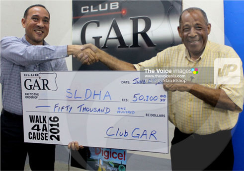 img: Club Gar's Gordon Charles (left) presents SLDHA's George Eugene with the ceremonial cheque. [PHOTO: Stan Bishop]