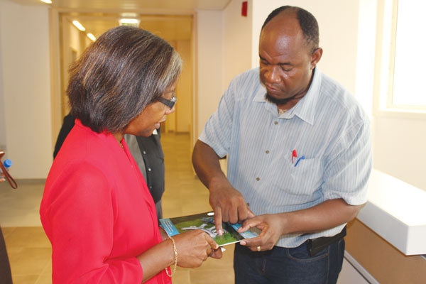img: Minister Issac studies a piece of hospital equipment