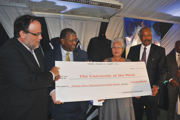 img:(l-r) Senator Mark Golding, an Oxford graduate; Donovan Walker, Partner, Hart, Muirhead & Fatta, Attorneys-at-Law; Lady McIntyre, wife of Sir Alister McIntyre and Sir Hilary Beckles, Vice-Chancellor of The University of the West Indies with the cheque for US$35,000 donated by Oxford graduate and Attorney-at-Law, Hugh Hart, to the McIntyre/Nettleford Scholarship Fund.