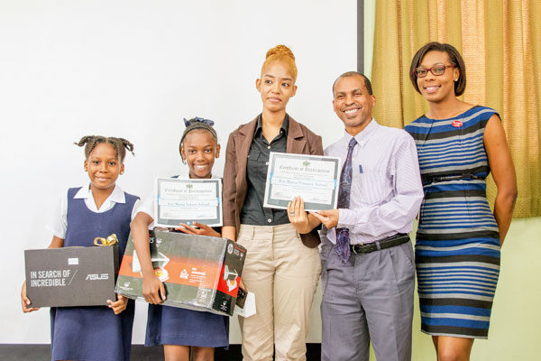 Image: Ms. Victor (right) with school winners