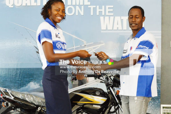 Image: Oswald Simon receiving the keys for his brand new Yamaha bike from K.L. Marines Operation Supervisor Cathy Gaspard (Photo Anthony De Beauville)
