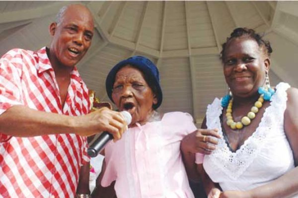 "Image: Terrence ""Cosol"" Alexander (left) sharing the microphone with a former La Rose chantwell at last year's grand fete in Vieux Fort Square."