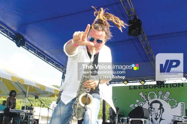 "Image: Saxophonist Rob ""Zii"" Tylor pays tribute to Leebo with music and the Leeboration movement's signature ""L"" sign. (PHOTO: Stan Bishop)"