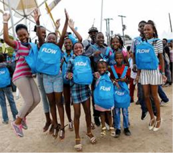 img: Students pose for the cameras with their brand new school bags received at FLOW Skool Aid 2016.