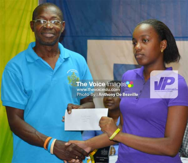 Image: (L-R) Youth and Sports Officer Lgorious Marquis presenting Vionce Weeks, daughter of former national footballer Victorin Weeks, with her scholarshipo fund. (PHOTO: Anthony De Beaville)