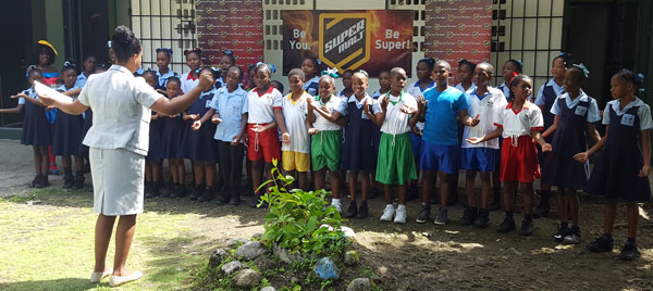 img: La Croix Maingot Combined School choir performing after receiving  a suprise donation from SuperMalt.