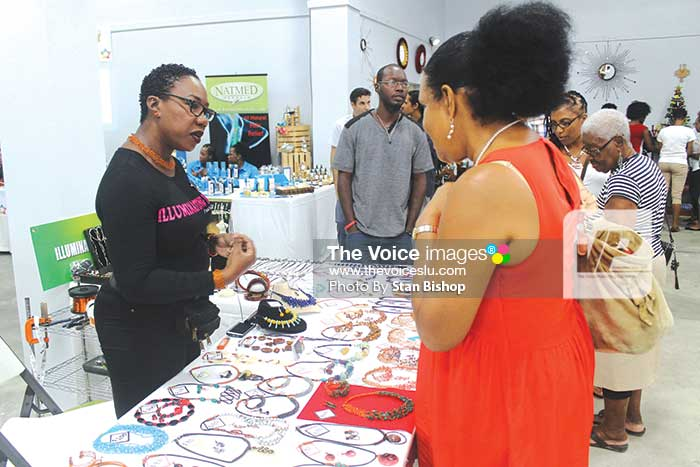 Image: Terril Nicholas (left) explaining to a curious customer some of the items she specializes in. [PHOTO: Stan Bishop]