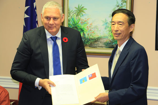 img: A moment of transparency - Prime Minister Allen Chastanet and Taiwanese Ambassador Ray Mou display agreement at signing ceremony.