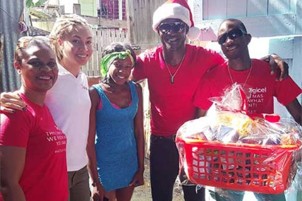 Image: Digicel Country Manager and Brand ambassadors gifts single mother.