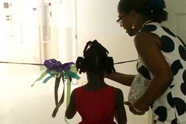 Image: Minister Isaac and a young girl cut the ribbon to open the unit.
