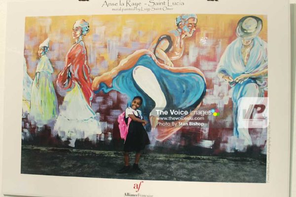 Image: Schoolgirl captured in Maillet-Contoz's photo of a mural painted by Luigi St. Omer in Anse la Raye. [PHOTO: Stan Bishop]