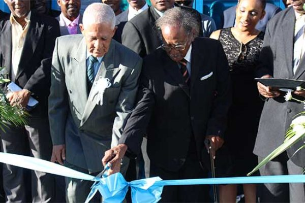 Image: The symbolic ribbon cutting was performed by two founding fathers of the St. Lucia Co-operative League, namely Emmanuel Theodore (L) and Haydn Williams. [PHOTO: By PhotoMike]