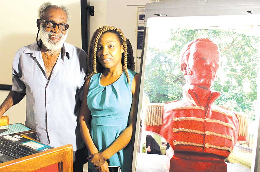 Image of Dr. Gregor Williams and Joanna Andrew next to a portrait of Jean Baptiste Bideau. [PHOTO: Stan Bishop]