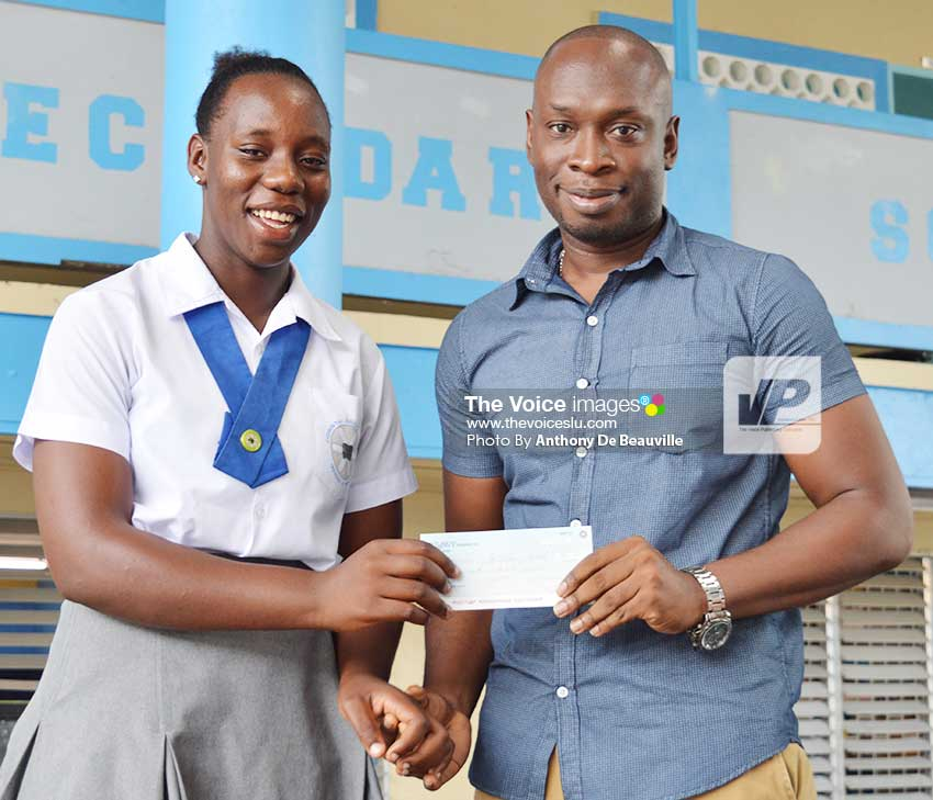 Image: (l-r) Qiana Joseph receiving a $500.00 cheque from Beauty Max's Nickson Pierre