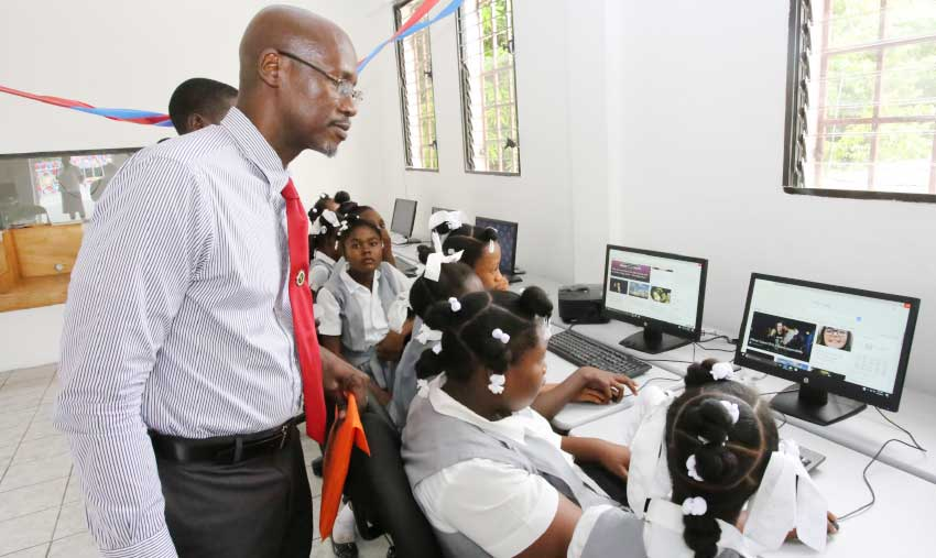 Image: Students using the computer equipment donated by ECTEL as Managing Director Embert Charles looks on.