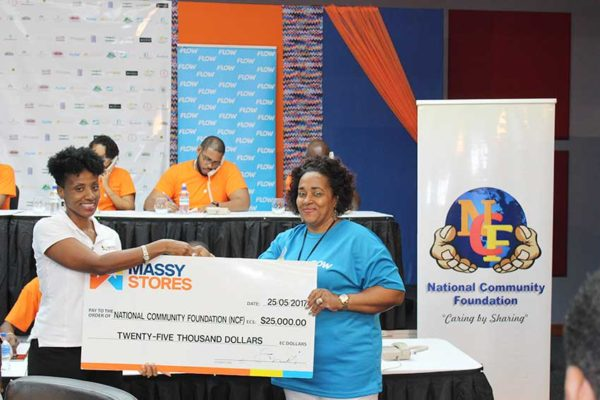 Image: Massy Stores' Sariah Best-Joseph pledging the company's $25,000 contribution to NCF's Executive Director, Michelle Phillips.