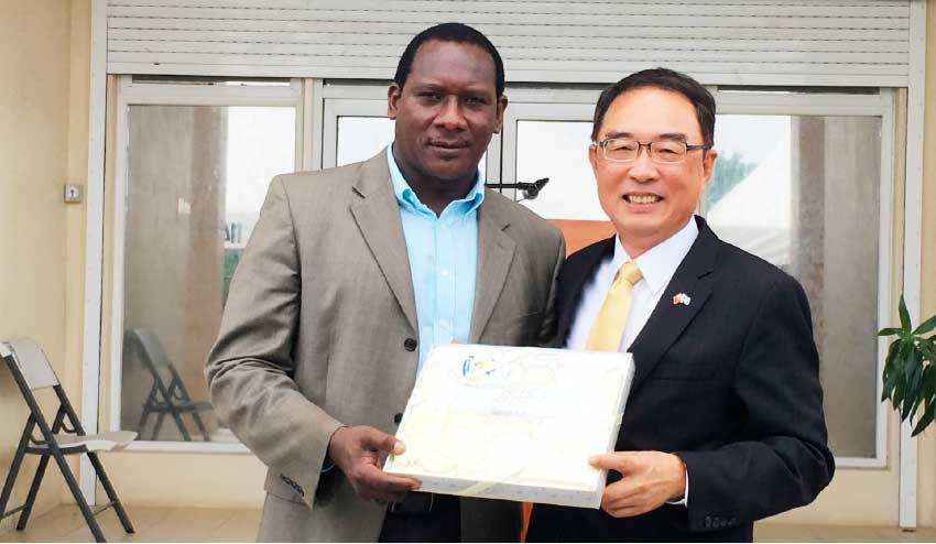 Image: Minister Montoute and Ambassador Shen display one of the items donated by Simplyhelp Foundation.