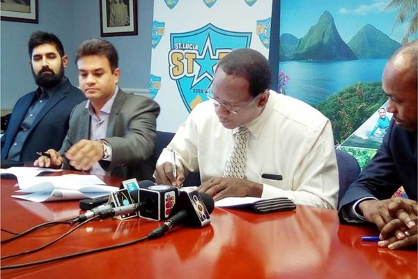 Image: Pandya and Montoute sign the agreement yesterday. [PHOTO BY PhotoMike]