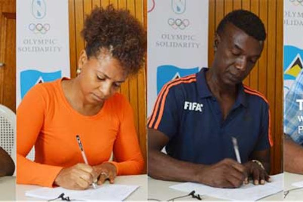 Image: (L-R) Some of the signatories, Roger Butcher (Rugby), Rochelle Jn. Baptiste (Athletics), Cess Podd (SLFA) and Oliver Lawrence (Karate) signing documents indicating receipt of funding from the SLOC. (Photo: Anthony De Beauville)