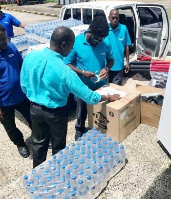 Image: Saint Lucia Country Manager Chris Williams helps pack supplies for Dominica.