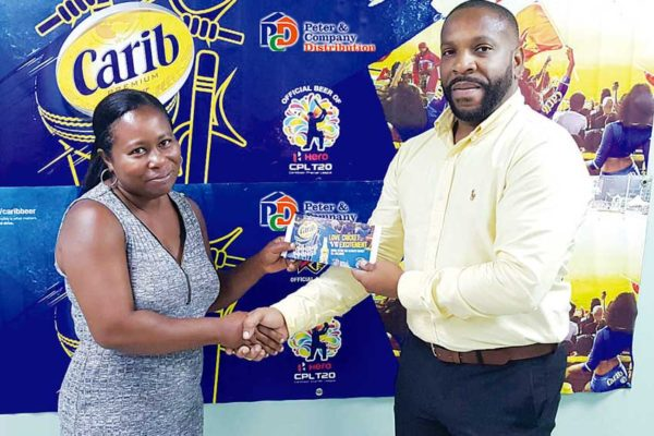 Image of Genifer Madsen (left) receiving her travel package from Carib Beer Brand Manager at PCD, Germaine Serieux.