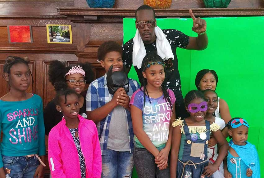 Image: Mac 11 and the children during a photo op at the event.