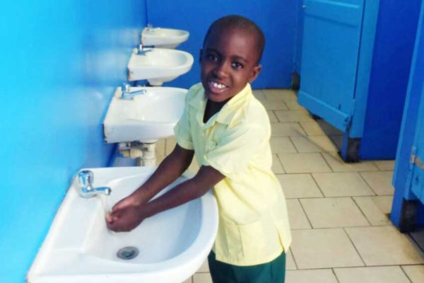 Image of one of the Balata Government School students making use of the refurbished bathroom facility at his school.
