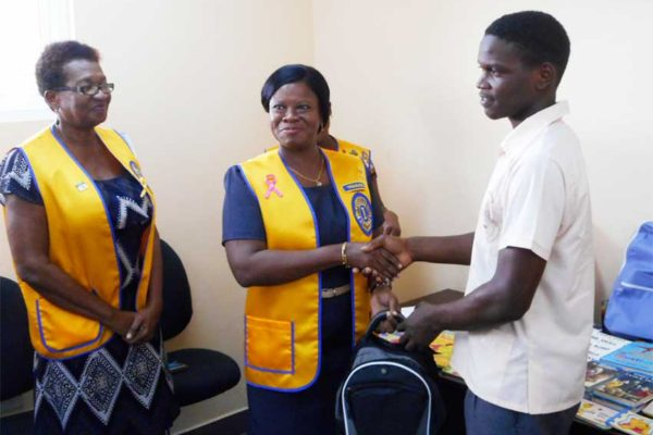 Image of A student of Micoud Secondary School receiving his backpack from a member of the Lions Club of Micoud.