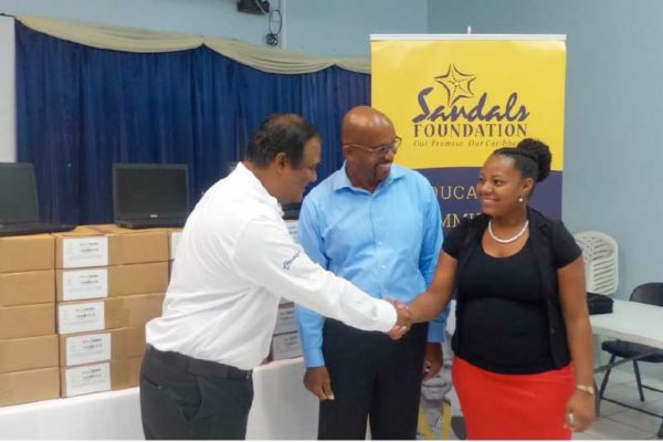 Image: Regional Public Relations Manager for Sandals Resorts in the Eastern Caribbean, Sunil Ramdeen, (left) presents the 20 laptop computers to TSOBE officials on Monday.