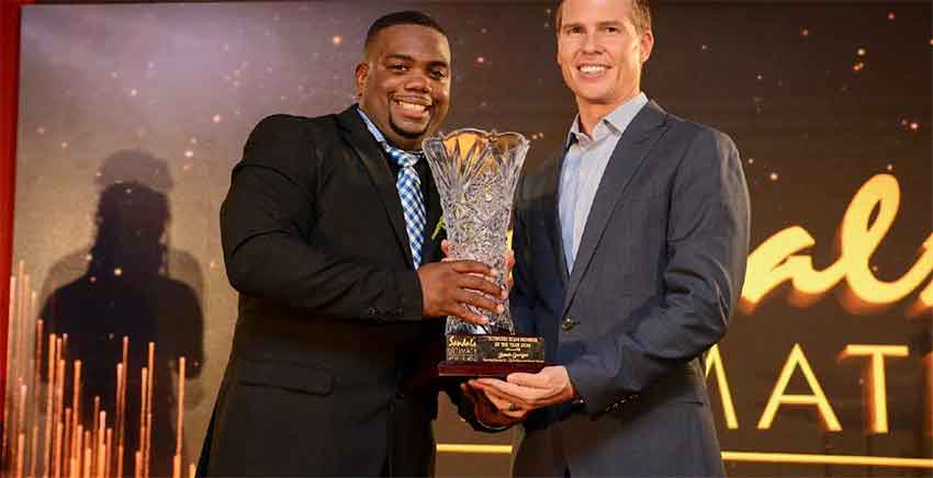 Image: Jamer Georges, the Ultimate Team Member of the Year for the Sandals ATL Group, pauses from his usual energetic antics to collect the top trophy from the company's Deputy Chairman and CEO, Adam Stewart.