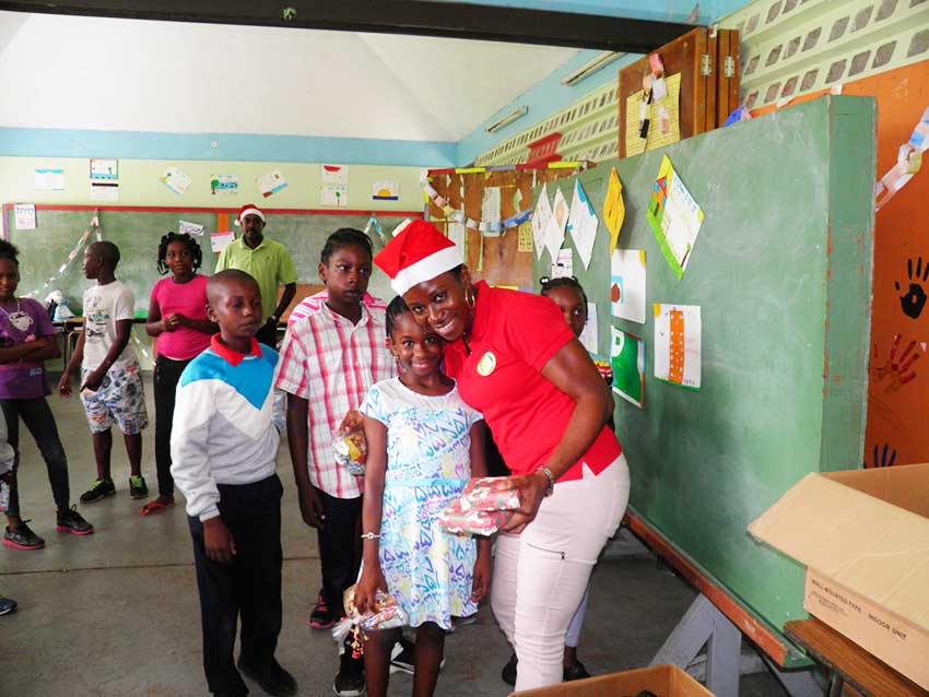 Image: OECS Staff distributing gifts during the Toy Drive to Dominica.