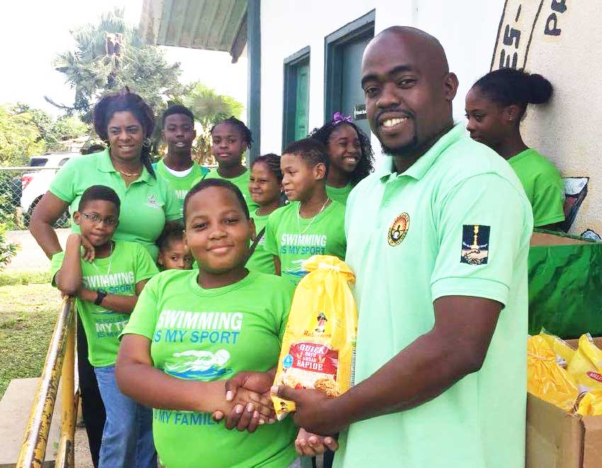Image: A young male swimmer from LASC presenting a food item to school principal, Ezra Joseph. (Photo: LASC)