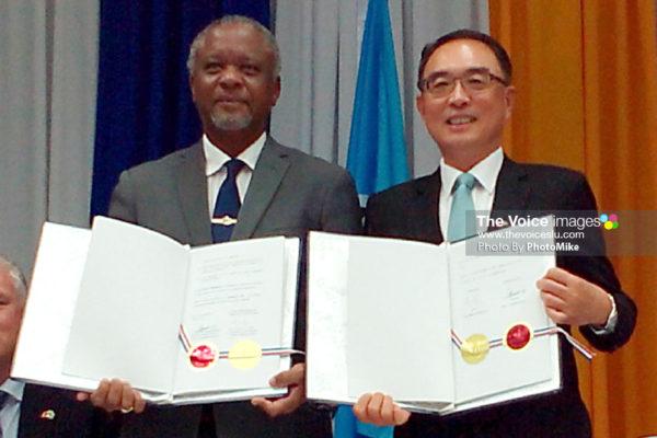 Image of Minister Francis (left) and Ambassador Shen holding up the signed documents. (PHOTO: PhotoMike)