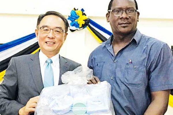 Image of His Excellency Ambassador Douglas Shen handover the sample of charity supplies to the Honourable Lenard Montoute
