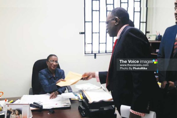 Image of Opposition Leader Philip J. Pierre submitting the draft motion to the Clerk of Parliament on Tuesday. (PHOTO: PhotoMike)